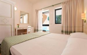 A bed or beds in a room at Camping Village Capo D'Orso