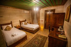 A bed or beds in a room at Hermes Cave Hotel