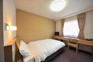 A bed or beds in a room at Dormy Inn Express Soka City