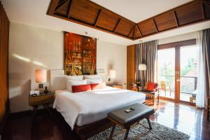 A bed or beds in a room at RatiLanna Riverside Spa Resort