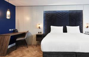 A bed or beds in a room at Roomzzz Newcastle City
