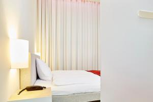 A bed or beds in a room at Greulich Design & Lifestyle Hotel