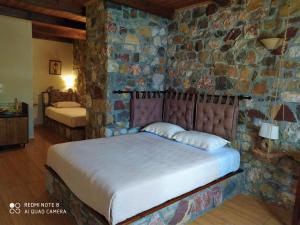 A bed or beds in a room at Ataviros Hotel