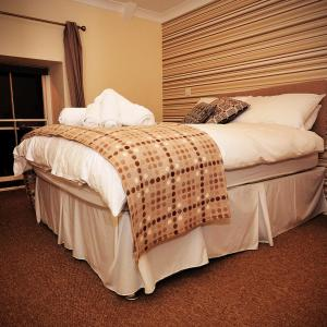 A bed or beds in a room at The Nags Head Inn