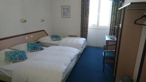 Un ou plusieurs lits dans un hébergement de l'établissement Hôtel Les Deux Porches