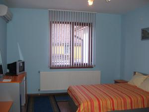 A bed or beds in a room at Kestenite Family Hotel