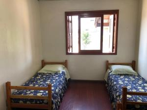 A bed or beds in a room at POUSADA LOCATELLI