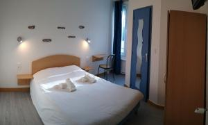 A bed or beds in a room at Hôtel des Sables Blancs