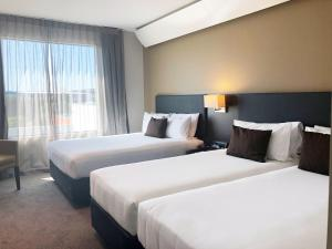 A bed or beds in a room at Sudima Auckland Airport