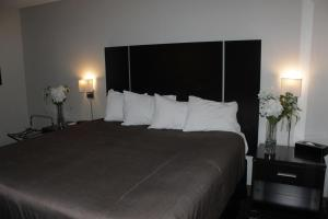 A bed or beds in a room at Ramada Plaza by Wyndham Niagara Falls