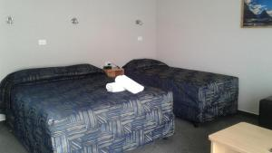 A bed or beds in a room at Parklands Motel