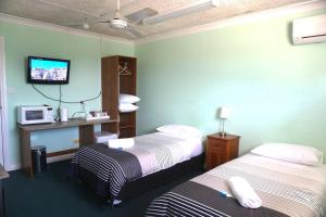A bed or beds in a room at Warners Bay Hotel
