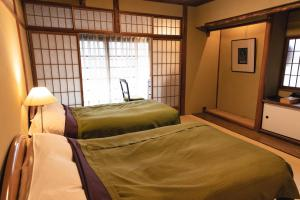 A bed or beds in a room at Hotel Hanakoyado