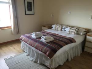 A bed or beds in a room at Longhouse Cottages