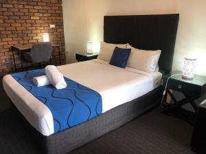 A bed or beds in a room at Logan City Motor Inn