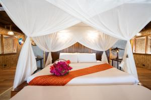 A bed or beds in a room at Flower Island Resort