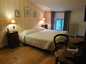 A bed or beds in a room at Hotel Logis - Chateau de Beauregard