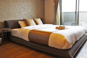 A bed or beds in a room at Ostay Vermillion Namba