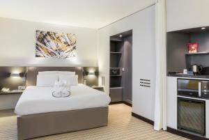 A bed or beds in a room at Novotel Suites Paris Roissy CDG