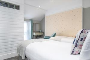 A bed or beds in a room at Beachside Guest House
