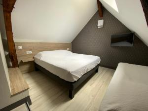 A bed or beds in a room at Hôtel Saint Nicolas