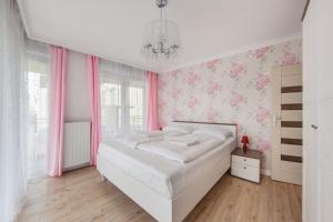 A bed or beds in a room at Apartamenty Sun & Snow Promenada