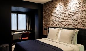 A bed or beds in a room at Hotel Louvre Lens - Esprit de France