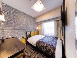 A bed or beds in a room at APA Hotel Hiroshima-Ekimae Ohashi