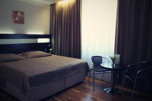 A bed or beds in a room at Galaxie Hotel