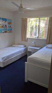 A bed or beds in a room at Mermaid Beach Apartment