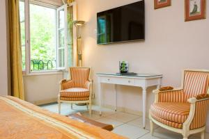 A television and/or entertainment center at Hôtel & Spa Greuze - Room Service Disponible