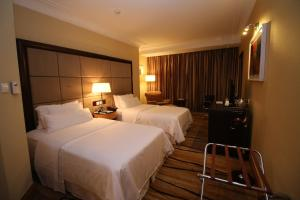 A bed or beds in a room at The Westin Dhaka