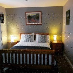 A bed or beds in a room at The Rose Garden Bed & Breakfast and Cafe