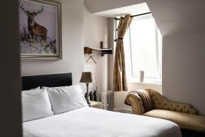 A bed or beds in a room at Whitebridge Hotel