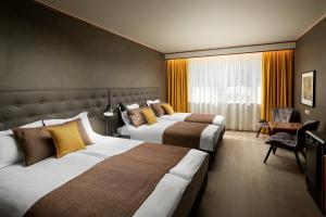 A bed or beds in a room at Hotel Ísland – Spa & Wellness Hotel