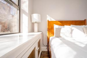 A bed or beds in a room at The High Line Chelsea 30 Day Rentals