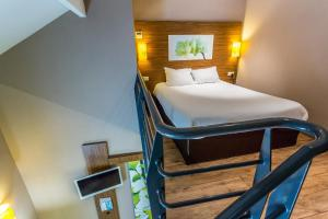 A bed or beds in a room at ibis Styles Bourges