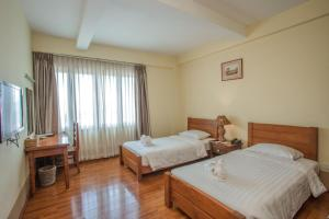 A bed or beds in a room at Shwe Ingyinn Hotel Mandalay