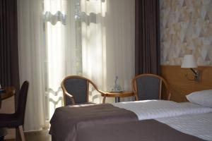 A bed or beds in a room at Amber Sea Hotel & Spa
