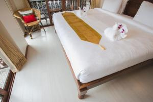 A bed or beds in a room at Chada Mantra Hotel