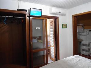 A television and/or entertainment center at Ex Pousada Vale do Bosque - Aluguel por temporada