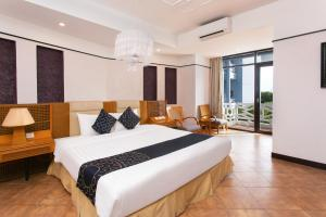 A bed or beds in a room at CAPITAL O 1078 Sun & Sea Resort Hue
