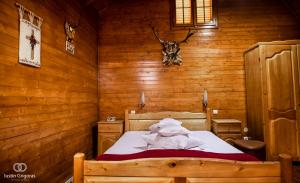 A bed or beds in a room at Pension Vanatorul
