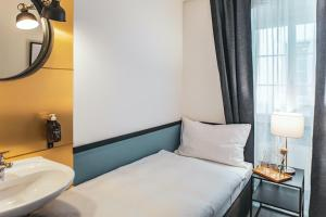 A bed or beds in a room at Pop Up Hotel Krone Zürich