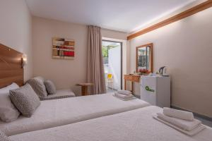 A bed or beds in a room at Dionysos Hotel