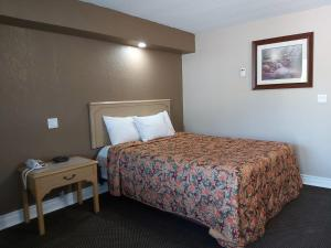 A bed or beds in a room at Arnprior Motor Inn