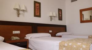 A bed or beds in a room at Hotel Restaurante Blanco y Verde