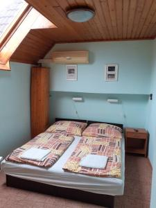 A bed or beds in a room at Júlia Vendégház