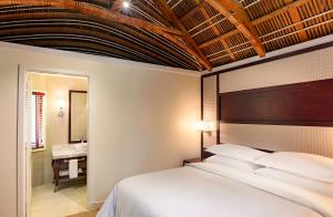 A bed or beds in a room at Sheraton Samoa Aggie Grey's Hotel & Bungalows