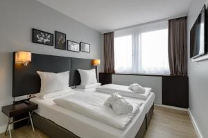 A bed or beds in a room at Mercure Hotel Potsdam City
